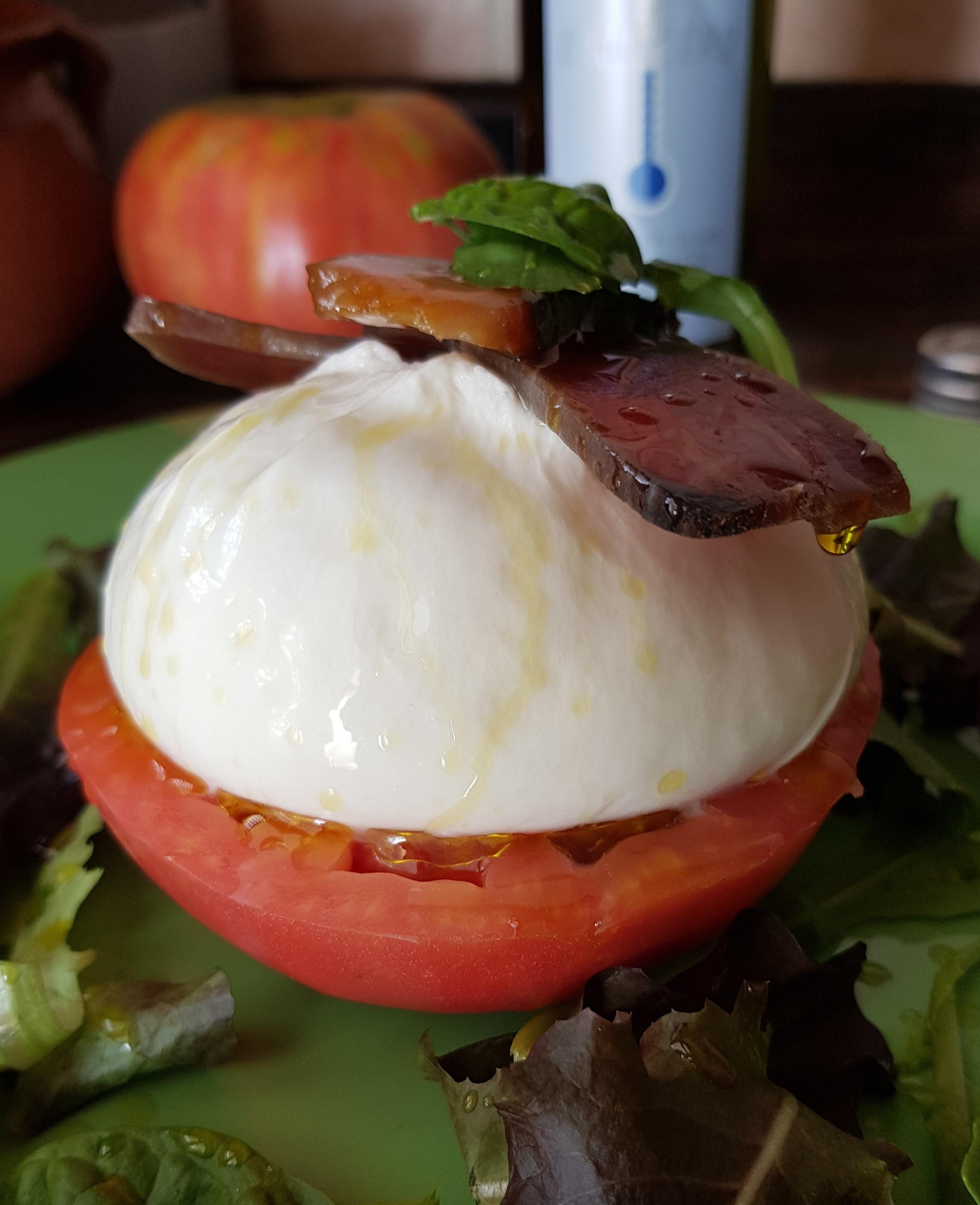 Ensalada gourmet con aceite de oliva virgen extra bajo cero, tomate , burrata y salazones